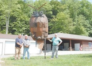 Mitch Whitaker, Nolan Bennett and Doug Adams took creating an owl out of recyclables to new heights by welding a 12-foot tall great horned owl. The sculpture was installed near the wildlife rehabilitation and education center at the Letcher County Extension Office. The figure, which is made of 10-speed bicycle rims, aluminum, tin and metal scraps, is part of the Interactive Art Festival. Twelve horned, barred and screeched owls are living in the center seen at right. (Photo by Sally Barto)