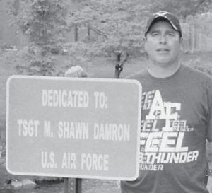 Pictured is Shawn Damron, a retired member of the U.S. Air Force Security Forces, beside a veteran's sign dedicated in his honor and placed at Camden Road in Jenkins. He is a son of the late Doug and Jackie Damron of Jenkins, and lives in Billings, Mont., with his wife, Jennifer, and children, Harley, Cheyenne and Jayden.