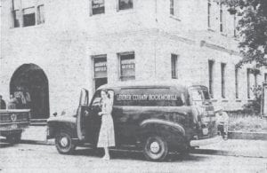 """The front page of the May 28, 1953 edition of The Mountain Eagle featured a photograph of the Letcher County Public Library's first """"Bookmobile."""" The photo shows the vehicle and its driver, Mrs. Follace Fields of Whitesburg, in front of the Letcher County Courthouse. The vehicle was driven to Whitesburg by State Sen. Archie Craft."""