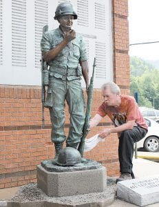 """Artist Sam McKinney, a 1969 graduate of Fleming-Neon High School, polished """"Freedom's Price"""" on June 7. The dog tags being held by the soldier were made from a cast of dog tags that belonged to McKinney's father, a World War II veteran of the Normandy Invasion."""
