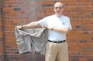 Retired teacher Paul David Sturgill lost 100 pounds in 20 months after becoming the only male member of a Weight Watchers group that meets in Whitesburg. Sturgill is seen here displaying a pair of short pants he wore when he weighed 301 pounds. He now weighs 201. Related story inside. (Photo by Sally Barto)