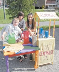 Jesse Cook, 8, Lexi Pease, 11, and Ravin Isom, 15, set up a lemonade stand at the farmers' market in Whitesburg on July 13.