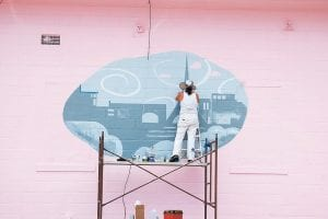 Mural artist Janet Cornett, of Ulvah, has been busy painting a logo on the side of Annie's Frugal Finery, a consignment shop located at Pine Mountain Junction in Whitesburg. Cornett has been painting murals in eastern Kentucky for 13 years. (Photo by Sally Barto)