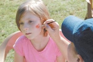 At right, a volunteer painted a heart on Hayley Day's cheek. Hayley, 9, a daughter of April and Brett Day of Bartesta Branch, will be a fourth-grade student at Cowan Elementary.