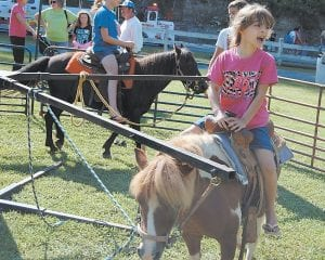 Six-year-old Trinity Faith Amburgey got a friend's attention while riding a pony at the Letcher County Kids' Day Back to School Bash at River Park in Whitesburg on July 26. Trinity is a daughter of Gary and Tisha Amburgey, of Loves Branch.