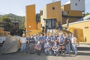 """Workers pictured in the photo at right are (back row, from left) James Gentry, Greg Ferris, Allen """"Doc"""" Fugate, Dave Creech, Cody Roark, Blake Breeding, Vernon Osborne, Steve Campbell, (front row, from left) William Potter, David Ashley, David Little, Garry Griffith, Jeff Duff, Oman Sandlin, Roger Cornett, Randy Fields, (kneeling, from left) Kirk Adams, Tom Biggs, and Artemus """"Tee"""" Campbell. The framed images on the step of the loader are three """"Centennial of Safety"""" awards the plant won from 2005, 2007 and 2008."""