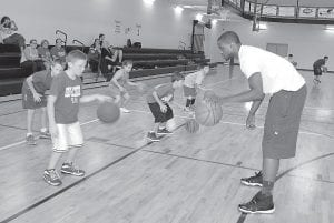 "Former University of Kentucky basketball star and current NBA player Darius Miller watched nine-year-old Landon Tolliver of Whitesburg practice dribbling during a short camp hosted by the 23-year-old Miller at the Letcher County Recreation Center on August 1. Miller, a 6'8"" native of Maysville, Ky., will soon begin his second season with the New Orleans Pelicans. Miller played in 53 games for the Pelicans last year, averaging 13.3 minutes per contest. (Photo by Sally Barto)"