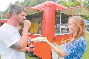 Plenty of food was also on hand during Saturday's festivities at McRoberts. Above, Devin Whitt offered a bite of funnel cake to her husband, Jason. At right, McRoberts resident Josh Treadway enjoyed a delicious hotdog.