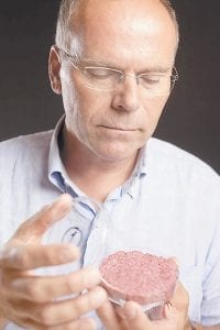 A new Cultured Beef Burger made from cultured beef grown in a laboratory from stem cells of cattle, is held by the man who developed the burger, Professor Mark Post of Netherland's Maastricht University. (AP)