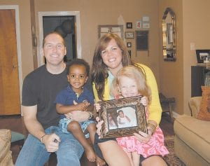 Pictured are Jonathan and Reagan Berry of Whitesburg with their children Addis and Stella. Stella is holding a picture of Kona, a one-yearold girl from the Democratic Republic of the Congo who they are in the process of adopting. The Berrys anticipate that they will be able to bring Kona home to Whitesburg by Christmas or the beginning of 2014.