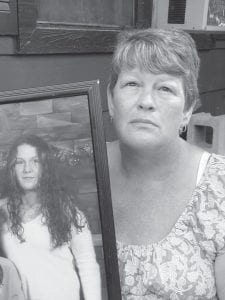 Tammy Ratiliff posed with a portrait of her daughter, Amy, a victim of Timothy Shelby's murderous rampage. (Photo by Bill Estep/Lexington Herald-Leader)