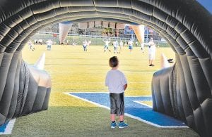 "Six-year-old Paxton Hammonds stood at the mouth of Letcher County Central High School's ""Cougar Tunnel"" admiring the 2013 team as they warmed up prior to last Friday night's season-opening game against Berea. Paxton, a Martha Jane Potter student, said that when he gets older he wants to be one of the Cougars playing on the field pictured in front of him. (Photo by Chris Anderson)"