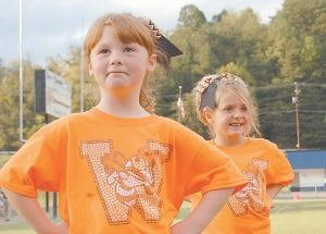 Kindergartener Emilee Johnson and first-grader Jauna McElroy waited to cheer for the West Whitesburg Elementary School football team Tuesday evening at the old Whitesburg High School football field, which is now home to the Letcher Central Middle School Cougars. (Photo by Sally Barto)