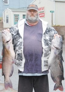 Dunham resident James Potter posed for this photo in Whitesburg Monday with two large blue channel catfish he caught at Fishpond Lake. (Photo by Sally Barto)