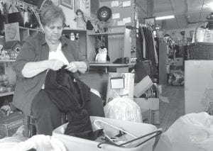 Cleda Turner, director of the Owsley County Outreach, folds clothes at the thrift store in Booneville in Owsley County, where food stamp cuts are taking their toll. (AP Photo/Dylan Lovan)