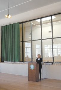 Holly B. Wiedemann, president of AU Associates, Inc., welcomed a large crowd Tuesday to a ribbon cutting and dedication ceremony for Jenkins School, which contains 26 one- and two-bedroom apartments for senior citizens who meet certain age and income guidelines. AU Associates preserved the 101-year-old Jenkins school building by transforming it into affordable housing. Located behind Wiedemann is the former school stage which is the new studio of the Letcher County government operated television channel.