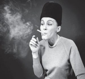 """In this 1964 photo, etiquette expert Cathy Bauby showed how puffing a cigarette like a steam engine shows that one is behind the """"Jet Age"""" and doesn't care how one looks, during a demonstration in New York. Fifty years on, health officials have begun to predict the end of cigarette smoking in America. (AP Photo)"""