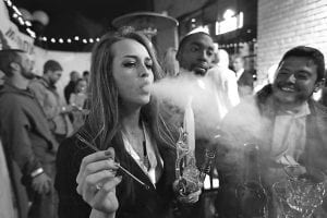 THE NEW NORMAL? — A woman smoked marijuana during a Prohibition-era themed New Year's Eve party at a bar in Denver, the day before Colorado allowed retail sales of marijuana to those 21 and over. Polls show that cigarette smoking is no longer considered normal behavior, and is now less popular among teens than marijuana. (AP Photo)