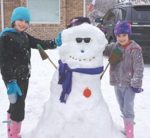 Sisters Olivia Frazier, 9, and Zoey Frazier, 7, posed with a snowman they built on Feb. 13. Olivia and Zoey are the children of Brian and April Frazier of Whitesburg.