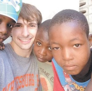 """""""Children would hang all over you wanting to hug you or hold your hand,"""" Jon Haynes, second from left, said of his visit to Haiti in January. Haynes lives and works in Letcher County."""