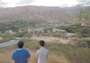 Jon Haynes, left, and a fellow volunteer stood on a hillside in Haiti overlooking the Children's Lifeline compound where he and other volunteers were based during their visit in January.