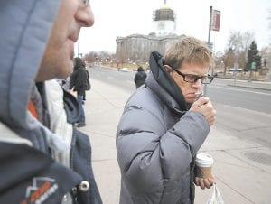 """Jason King lit a cigarette at a bus stop in Denver, with the Colorado state capitol building visible in the background. A bipartisan group of lawmakers in Colorado have proposed raising the legal age at which consumers may buy tobacco from 18 to 21. """"Ease up on the damn smokers!"""" said King, age 40, when interviewed on the subject. (AP Photo)"""