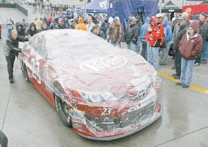 The crew for driver Alex Bowman (23) rolled his car with the rain cover on into the pit area prior to the NASCAR Sprint Cup series auto race at Bristol Motor Speedway on Sunday. (AP Photo/Wade Payne)