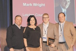 Chuck Osborne, Kentucky Farm Bureau Insurance Vice President of Agency Support & Marketing (left), and Tony Turner, KFB Insurance Agency Support & Marketing Manager for District Five (right), present Mark Wright (center right) and his wife, Ellena (center left), with the 2013 District Five Agency Manager of the Year Award.