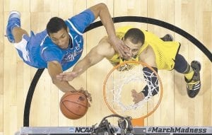 Kentucky's Marcus Lee, left, and Michigan's Jordan Morgan went after a rebound during the first half of the Wildcats' Midwest Regional final college basketball tournament win in Indianapolis on Sunday. Lee, a surprise star off the bench in the absence of Willie Cauley-Stein, will be called on Saturdy to help contain Wisconsin's 7-foot star Frank Kaminsky in Final Four action. The Kentucky-Wisconsin game set to tip off at 8:49 p.m. It will be telecast on TBS following the UConn-Florida game scheduled for a 6:09 tipoff. (AP Photo)