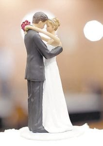 Figurines of a bride and a groom sit atop a wedding cake. A study of more than 3.5 million Americans finds that married people are less likely to suffer any type of heart or blood vessel problem. (AP Photo)