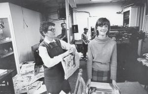 Pat Gish, left, was working with daughter Sarah to fold pages of The Mountain Eagle when this photo was taken during the late 1960s. Pictured in the background are husband Tom and son Ben running the press.