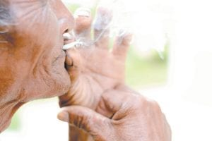 """An elderly man smokes marijuana. A new """"important but preliminary"""" study is the first to focus on possible brain effects among recreational pot smokers. (AP Photo)"""