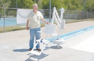 """Whitesburg Mayor James W. Craft tried out the newly installed pool lift at the Whitesburg Municipal Swimming Pool Tuesday afternoon. The handicap pool lift meets Americans with Disabilities Act (ADA) requirements. """"It's something that we have wanted to do for some time for our physically challenged people so they can enjoy the pool as well as everyone else,"""" said Craft."""