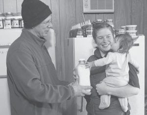 In this recent photo, dairy farmer Trevor Gilkerson handed customer, Amanda Owens, and her 5-month-old daughter, Mardi, a half-gallon of bottled raw milk on his family farm just outside of Brookings, S.D. Trevor partners with his father Jim Gilkerson on the Jerseydale farm. They sell most of their milk to a large production facility, but Trevor sells around 100 gallons of milk a week to about 50 local customers. Owens has been buying raw milk from Gilkerson since 2005.(AP Photo)