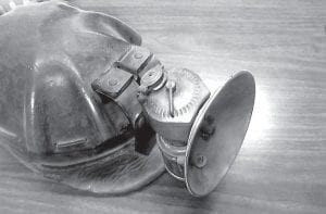A carbide lamp attached to a miner's hard hat. Note the leather bill on the hat.