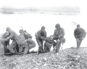 Members of an American landing unit helped their exhausted comrades ashore during the Normandy invasion, June 6, 1944. The men reached the zone code-named Utah Beach, near Sainte Mere Eglise, on a life raft after their landing craft was hit and sunk by German coastal defenses. (AP Photo)