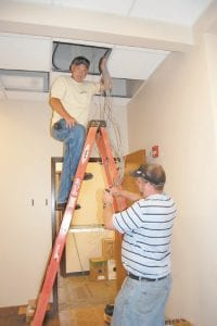Fabian Campbell and Nathan Strain, network technicians with the Commonwealth of Kentucky, installed wire Tuesday afternoon in the new offi ces of Letcher Commonwealth's Attorney Edison G. Banks II.