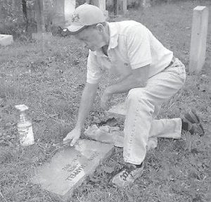 This 2008 file photo shows Jenkins resident Ked Sanders cleaning the grave marker of John Chappell, one of five victims of an 1892 massacre at Pound Gap. The graves of all five victims are located in Letcher County.
