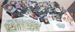 This photo shows the cash, oxycodone pills, Opana pills, synthetic marijuana and other drugs found in a Payne Gap home after the owner permitted a deputy sheriff to search it without a warrant. (Photo by Sally Barto)