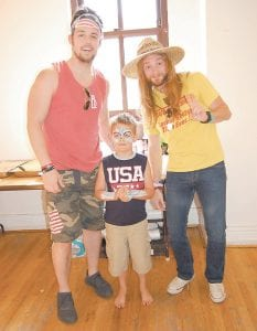 Six-year-old Peyton Hammonds posed for a photo with Nick Jamerson and Kris Bentley of Sundy Best on July 4 at Whitesburg City Hall. Peyton, a son of Robert Hammonds and Brandy Schweitzer, both of Whitesburg, had his face and arms painted to resemble an American bald eagle. Mayor James Wiley Craft said the city's July 4 celebration, with fireworks and a concert headlined by Sundy Best, drew the largest crowd on record to River Park. (Photo by Sally Barto)