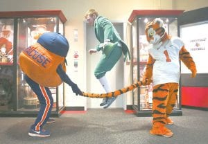 Syracuse mascot Otto the Orange, left, used the Clemson Tiger's tail as a jump rope for Notre Dame's Leprechaun before the start of the ACC news conference in Louisville last week. After bouncing around in three other leagues over 19 years, UofL is now a part of the ACC. (AP Photo/The Courier-Journal)