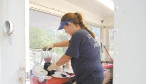 Colleen Combs, a cook at Letcher County Central High School, blended ice, yogurt and locally grown blueberries to make a blueberry smoothie for a child on July 12 at the Letcher County Farmers Market in downtown Whitesburg. Through the Summer Food Service Program and the Community Farm Alliance, breakfast burritos and blueberry smoothies are prepared on Saturday mornings at the farmers market in a mobile kitchen unit owned by Mountain Shrine Club. Most of the ingredients are bought locally from licensed growers. Children ages three to 18 are served breakfast burritos, blueberry smoothies and other items to complete a whole meal. (Eagle photos)