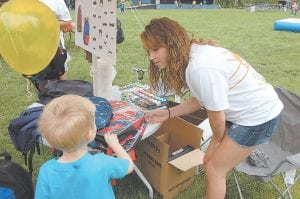 PUTTING OTHERS FIRST — Courtney Jackson, 16, of Jeremiah, helped a little boy pick out a new backpack at the Letcher County Kids' Day Back to School Bash on July 25 at River Park in Whitesburg. Courtney, who will be a junior at Letcher County Central High School, handed out nearly 90 backpacks before the event officially started at 10 a.m. Children were lined up in front of her table at 9 a.m. This is the second year that Courtney has organized a backpack drive for children in Letcher County. Courtney and her mother Daisy Jackson spent the rest of their time at the event painting mustaches on children's faces.