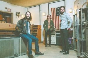 The Whigs are, from left, guitarist/vocalist Parker Gispert, drummer Julian Dorio, and bassist Tom Deaux. The band will perform Saturday in Whitesburg at Summit City. (Photo by Joshua Black Wilkins)