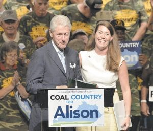 Former President Bill Clinton, left, was introduced to the audience in Hazard last week by Kentucky Democratic Senatorial candidate Alison Lundergan Grimes. Seated behind Clinton are members of the United Mine Workers Association, whose union has endorsed Grimes. (AP Photo/Timothy D. Easley)