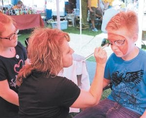 Face paint artist Mona Daylong decorated Dawson Rodriguez's face at the festival in Jenkins on Saturday.