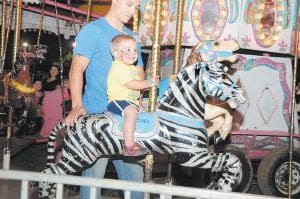 Cole Back smiled while taking a carousel ride under the watchful eye of his father, Josh Back.