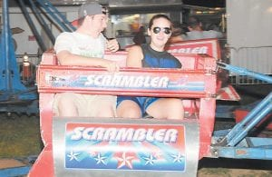 """Ethan Taylor, left, and Rachel Sexton enjoyed their turn on the traditional carnival ride known as the """"Scrambler."""""""