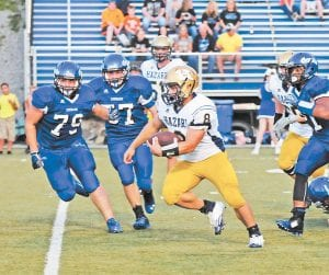 Hazard's Brandon Jones carried the ball deep in Letcher Central territory as Cougar defenders, from left, Triston Polly, Noah Brock and Jaylyn Williams, give chase. (Photo by Chris Anderson)