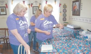 Above, volunteers Kathy Haselgrove, Trish Dekok (front) and Lela Abbatt (rear) sorted eyeglasses at the SmileFaith Community Dental Clinic. In photo below, Dr. Norma Jeanne Appelbaum, of Cape Coral, Fla.and assistant Diane Klien treat a patient Monday at SmileFaith Community Dental Clinic.